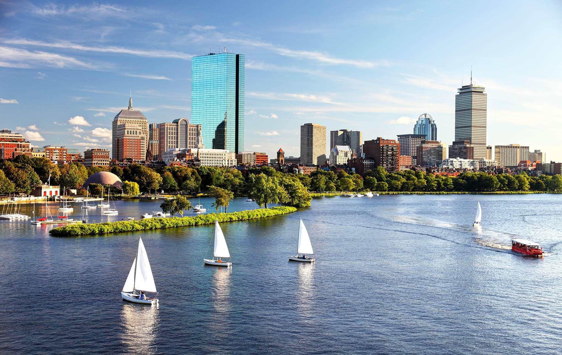 skyline view of boston with a tall blue glass building with river and green park and 3 sail boats