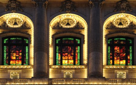 Three illuminated windows with stain glass red green and yellow a panels on ornate building