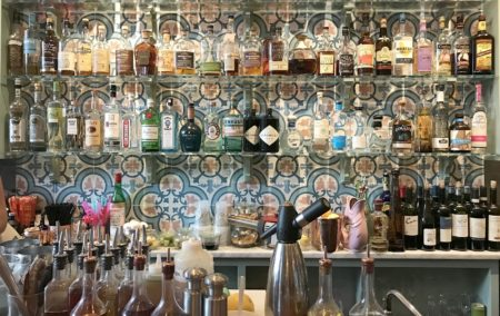 Colorful bar with bright blue tile and many bottles of alcohol