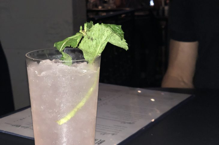 a pink cocktail with a spring of green mint next to a white menu that says black lamb