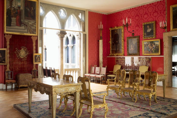red room with 6 gold chairs in the center and two gothic arches in the background