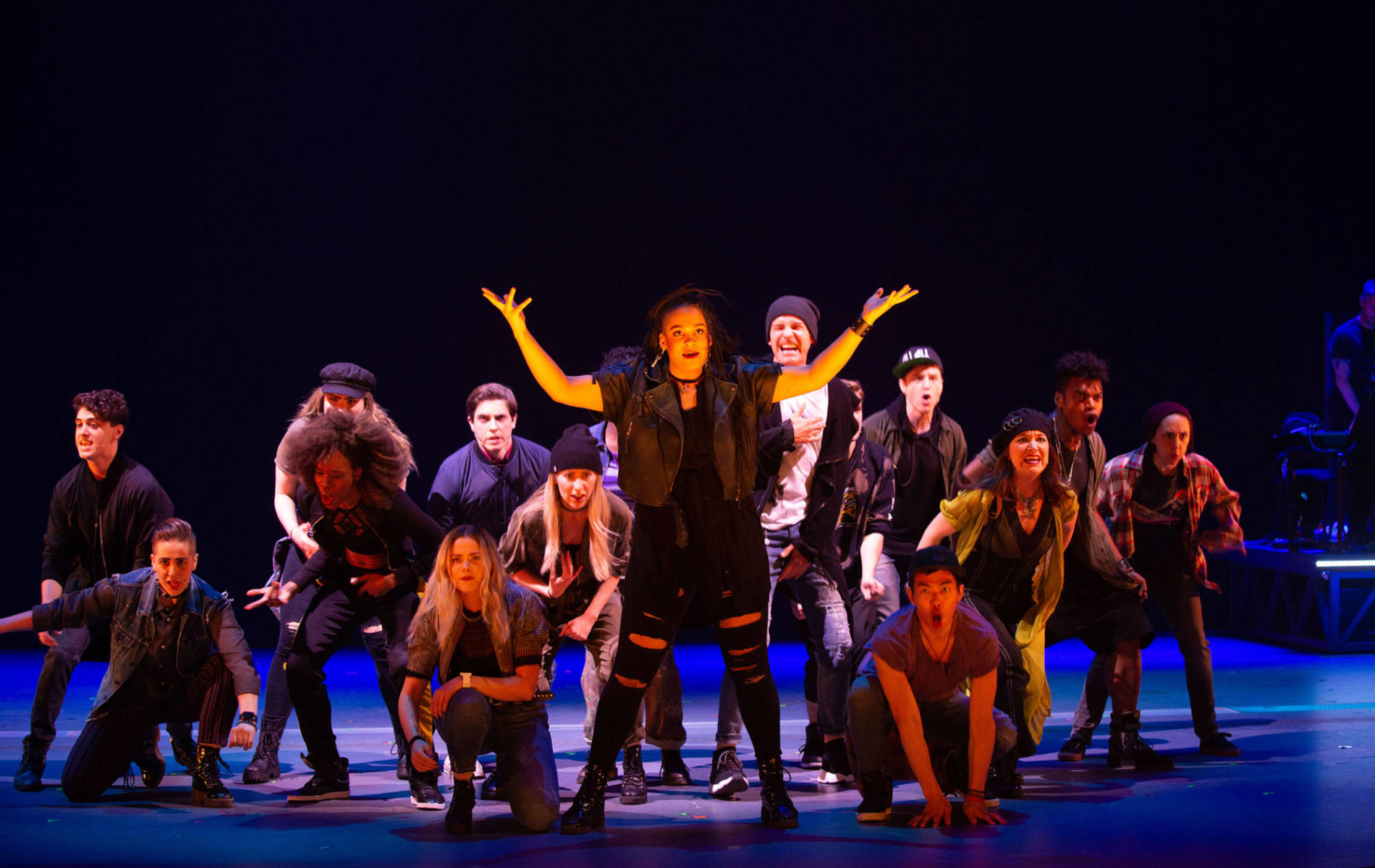 Cast performing on stage with blue lights and black background
