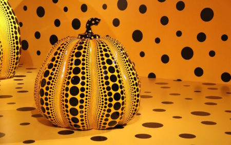 Orange pumpkin sculpture with black polka dots on same orange background with black dots