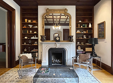 Victorian library with gold gilt mirror, marble mantle, walnut bookcases and modern furniture.