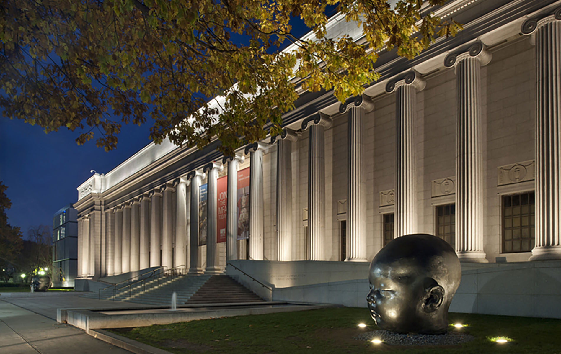 Museum with white columns at night with tree and gaint black state of a head