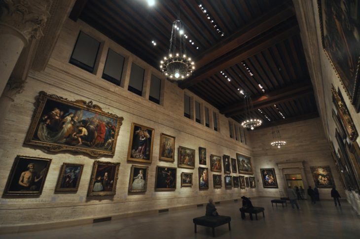 museum with tall ceilings and 3 chandeliers with a huge fall with about 20 old paintings