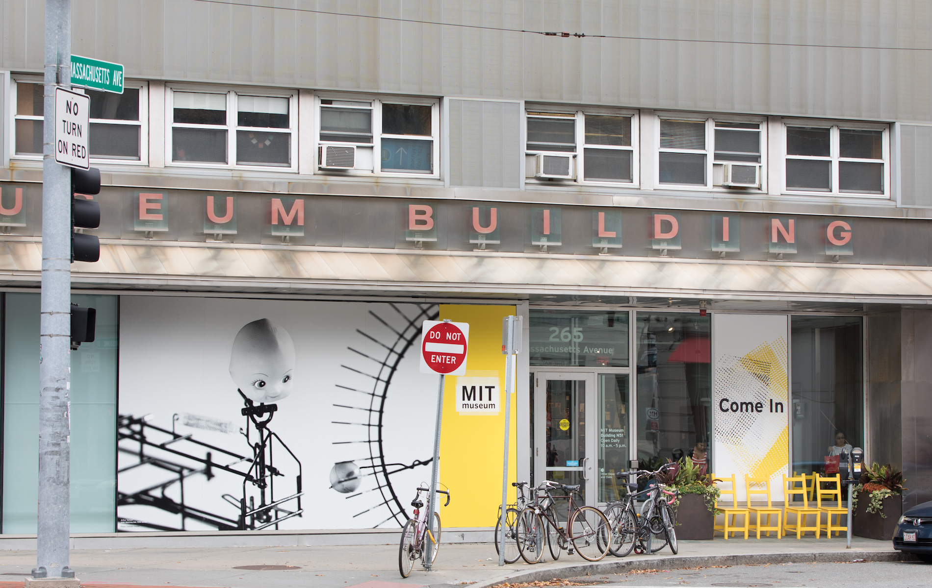 grey building that says museum with yellow sign next to door