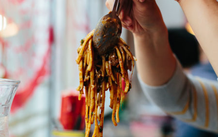 two hands lifting serving spoons full of golden noodles in a sticky brown sauce