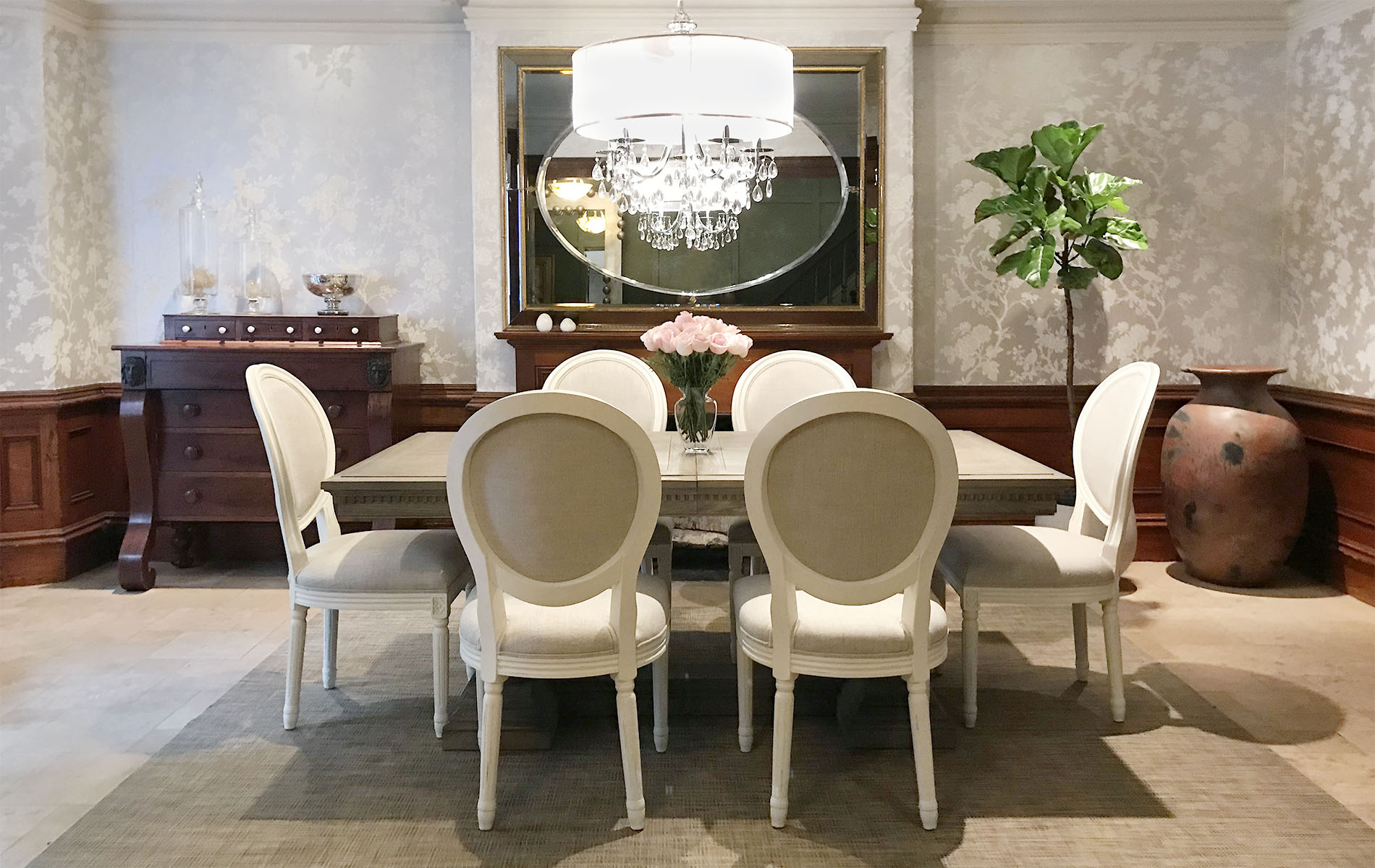 Dining room with silver wallpaper, mahogany paneling, oak table and 6 white wooden chairs with linen fabric