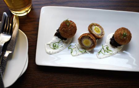 white plate with 3 scotch egg sliced in half next to glass of white wine
