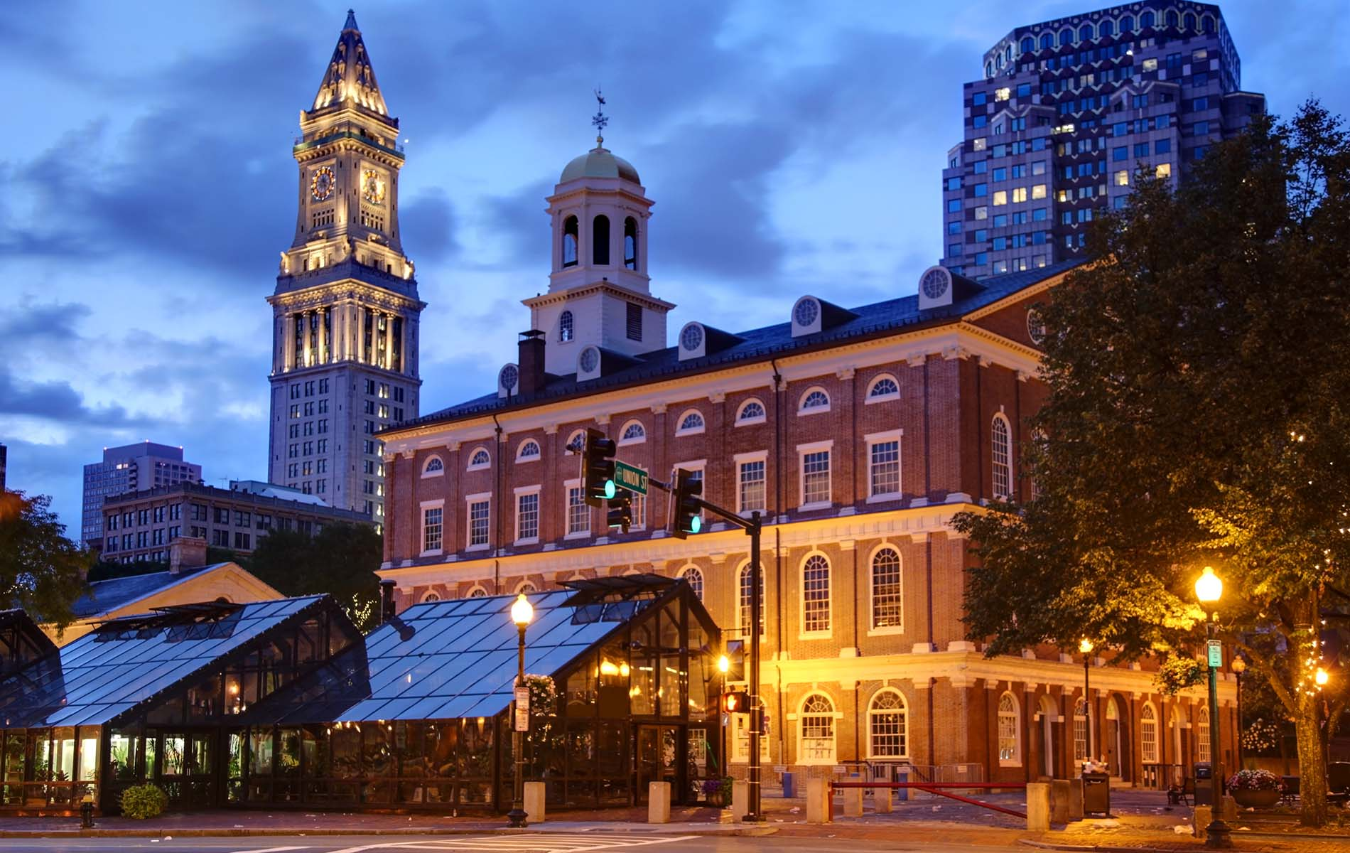 Night time sky with view of two illuminated towers on right and red brick building to left of quincy market