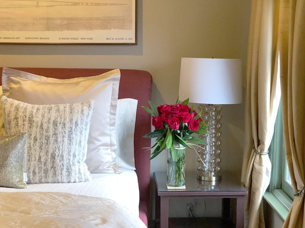 bed with two white and gold pillows with red head board and table with dozen red roses