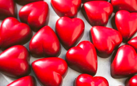 dozens of red chocolate truffles in a heart shape