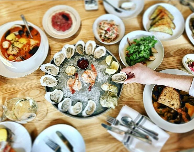 wooden table with various dishes with a ice plater in the center with a dozen oysters and a hand reaching for one