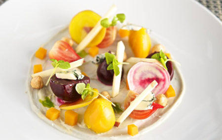 colorful plate of slice red and yellow beets and pieces of beef