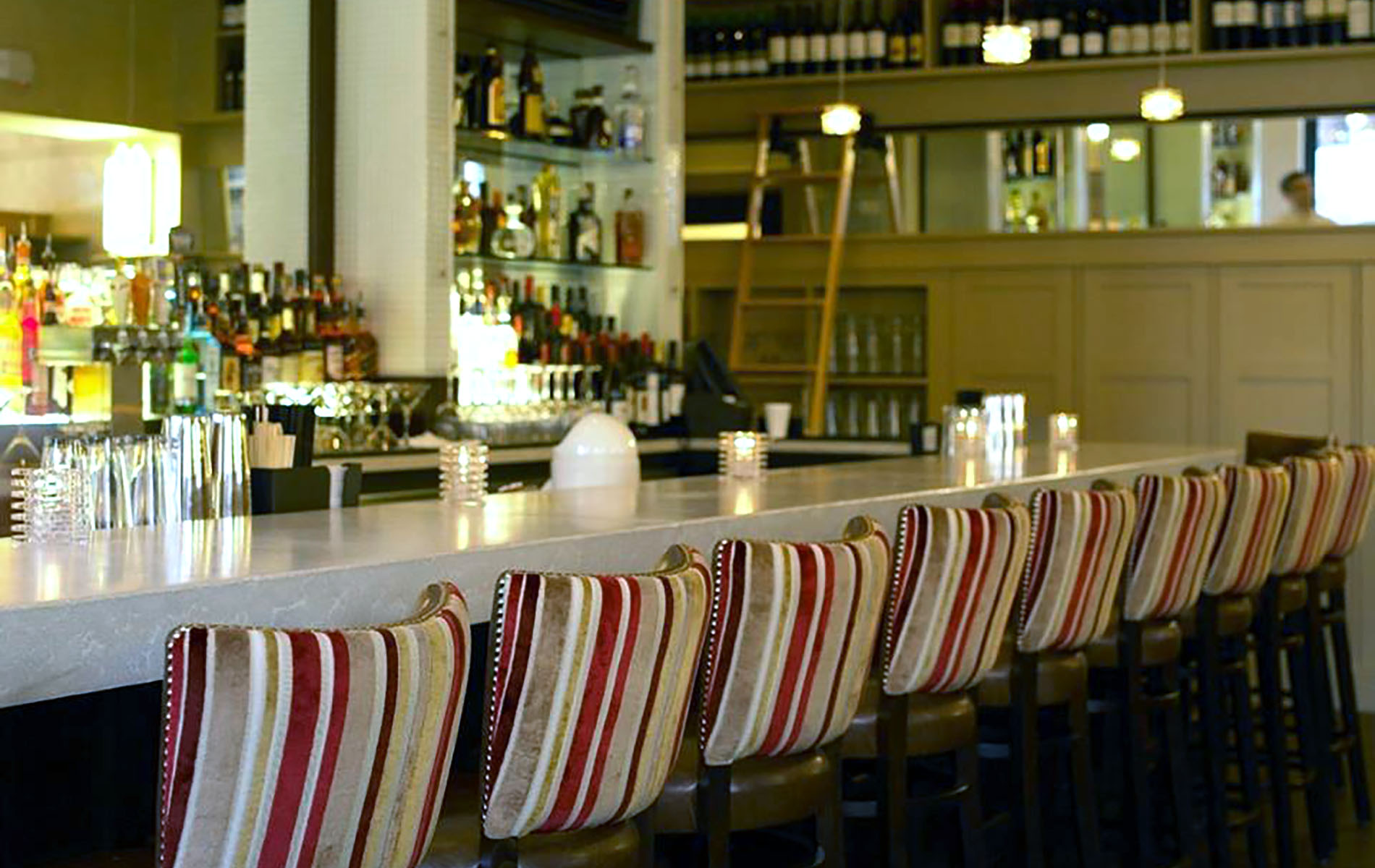 restaurant bar with white counter and red stripped chairs