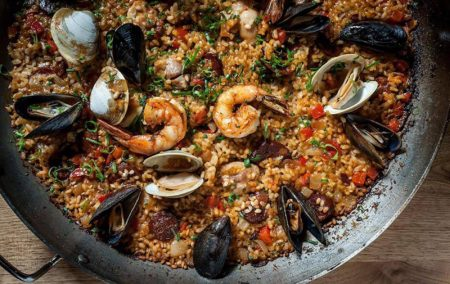 paella in a metal pan with black mussels and shrimp