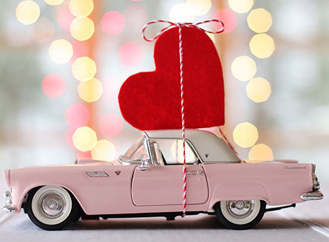 Pink vintage convertible with white roof and large red gift heart on top.