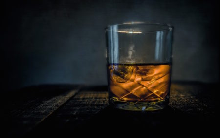 a cut crystal glass filled with golden brown whiskey on black background
