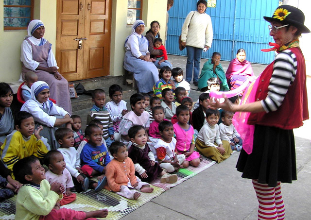 clown in red vest with black and white shirt performs for children in colorful outfits