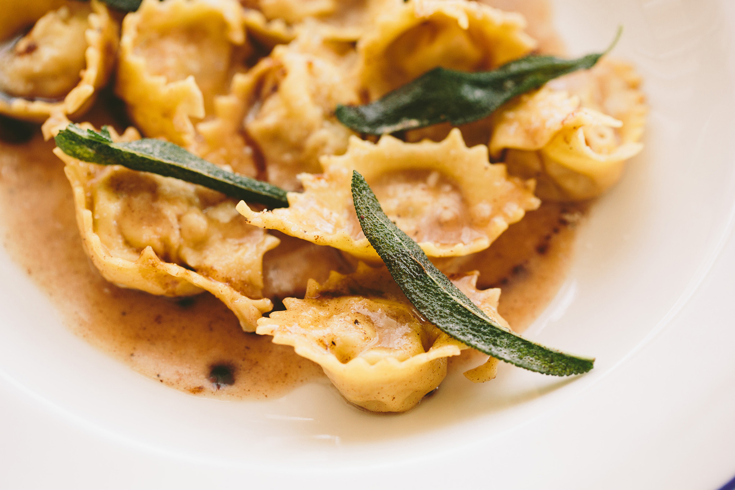 bowl of ravioli with 3 pieces of fried sage