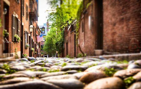 Ground level view of sloping stone alleyway between red brick buildings