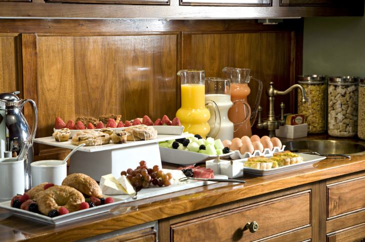 Breakfast bar with hard-boiled eggs, juice, jars of cereal, and white plates of fresh fruit, cheese, and quiche slices