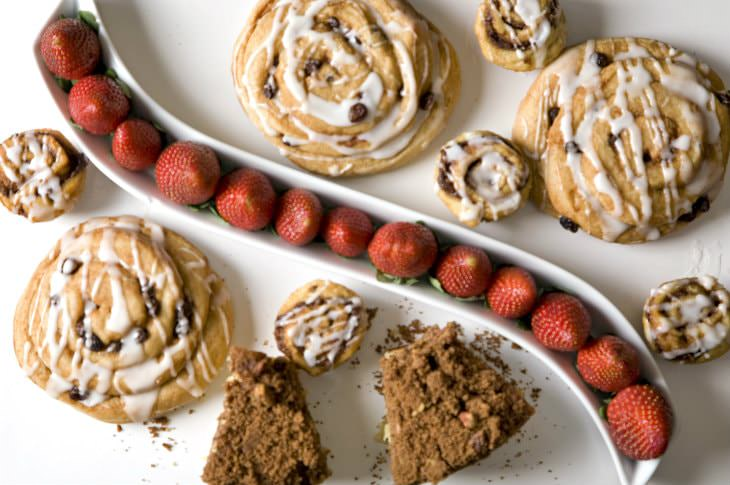 Iced rolls, scones and red strawberries on white dishes