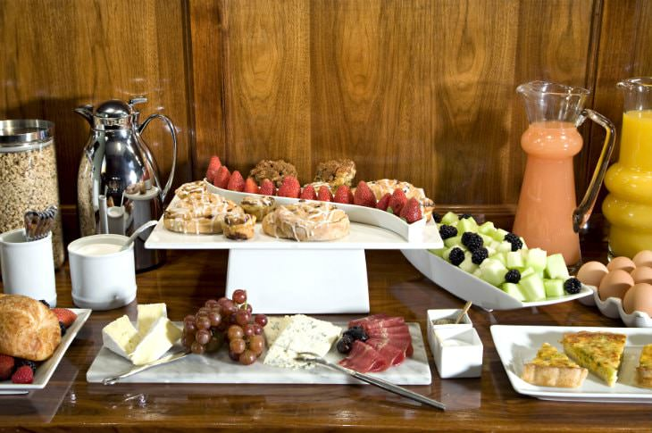 Breakfast bar filled with white plates of fresh fruit, cheese, quiche slices, eggs, juice, and silver carafe