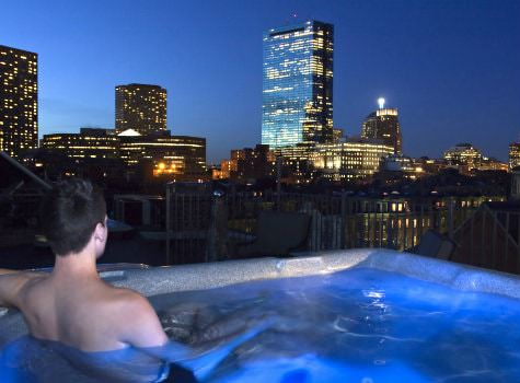 Man in roof top hot tub overlooking the dark blue sky and twinkling city at night