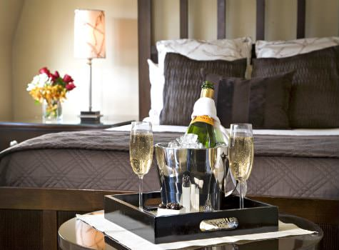 Elegant guest room in neutral colors with a tray of chilled champagne and glasses