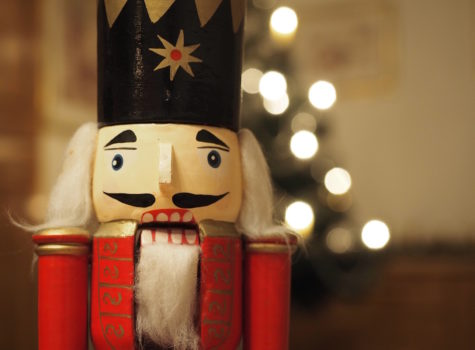 close up of a wooden nutcracker toy with black hat white beard and red body out of focus white lights behind