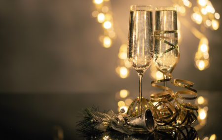 two glasses on champagne on the right with yellow lights behind and curled ribbon at base of glass