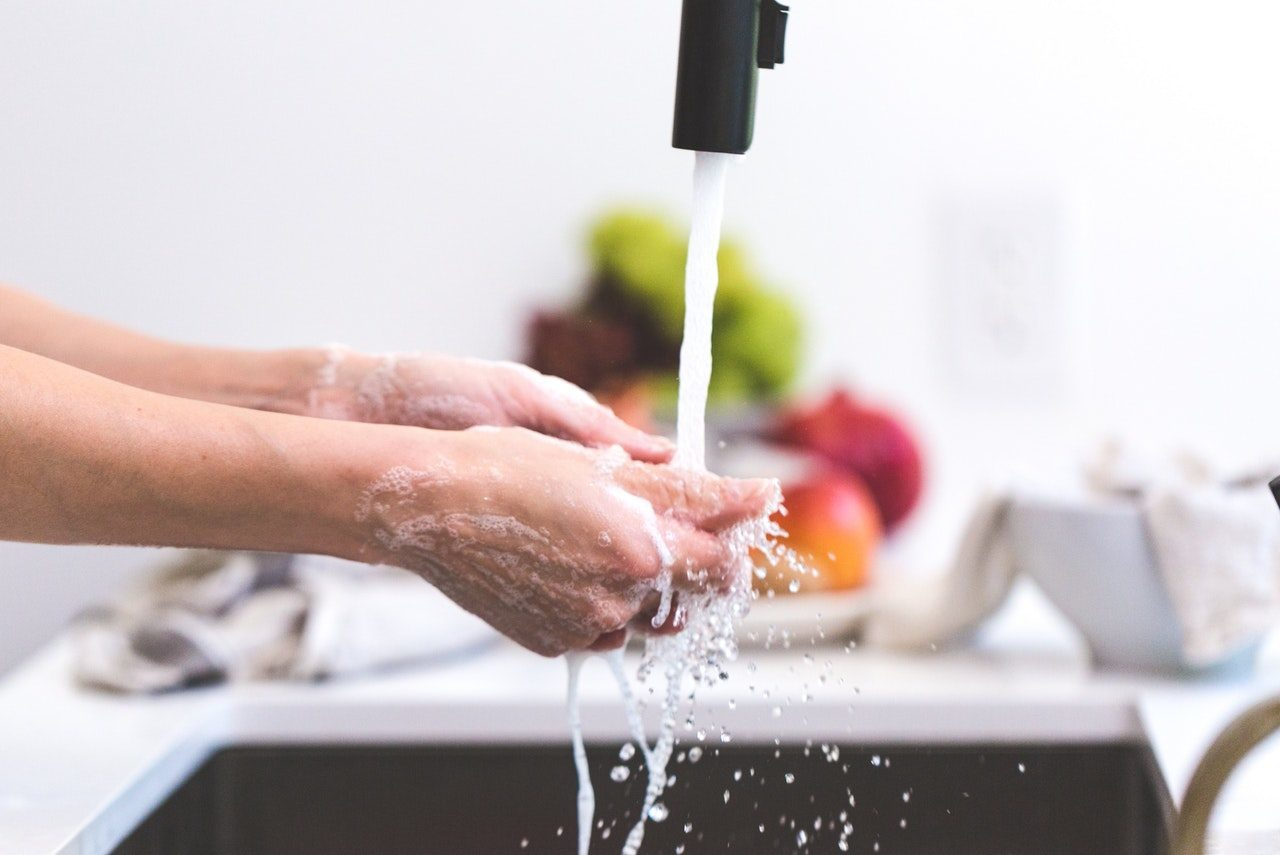 black faucet with running water two hands washing with fruit blurred in background