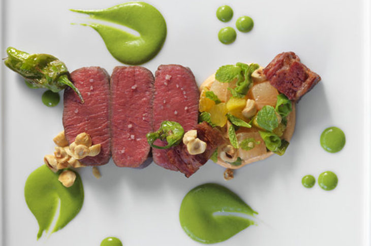 4 pieces of rare lamb with 3 circles of green sauce on white plate