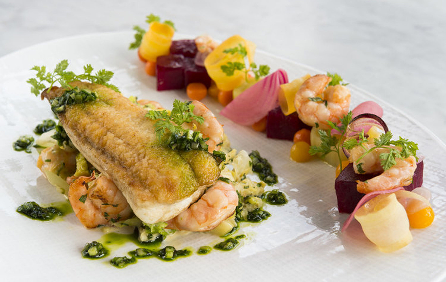fried fish on top of shrimp and dots of green sauce surrounded by beets and vegetables