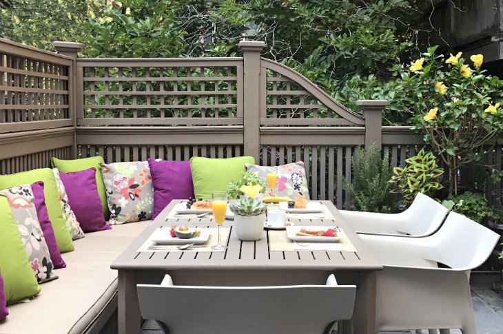 Gray patio table and chairs with bench seating topped with lime green and purple pillows