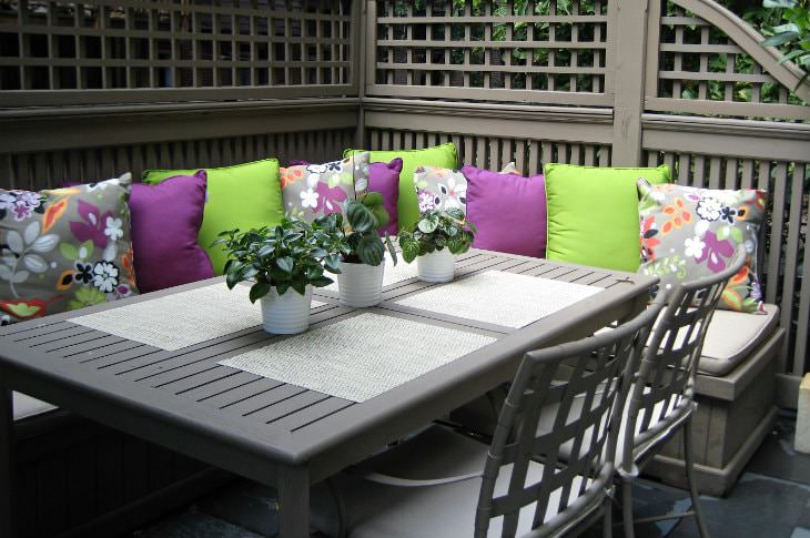 Gray patio table and chairs with wraparound bench seating topped with lime green, purple and floral pillows