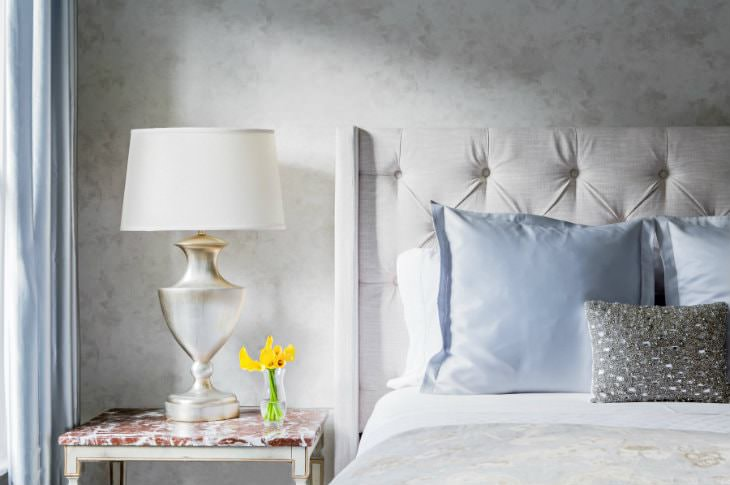 Bed with beige tufted headboard, white sheets and blue pillows, white nightstand with white-washed gold lamp and yellow flowers