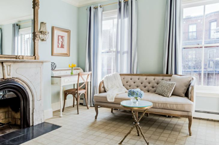 Light blue room with two large windows, fireplace, large mirror, secretary desk, and beige settee