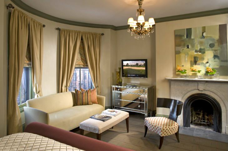 Cozy, elegant room with fireplace, gold chandelier, abstract art, and sitting area with mirrored chest and flat screen TV