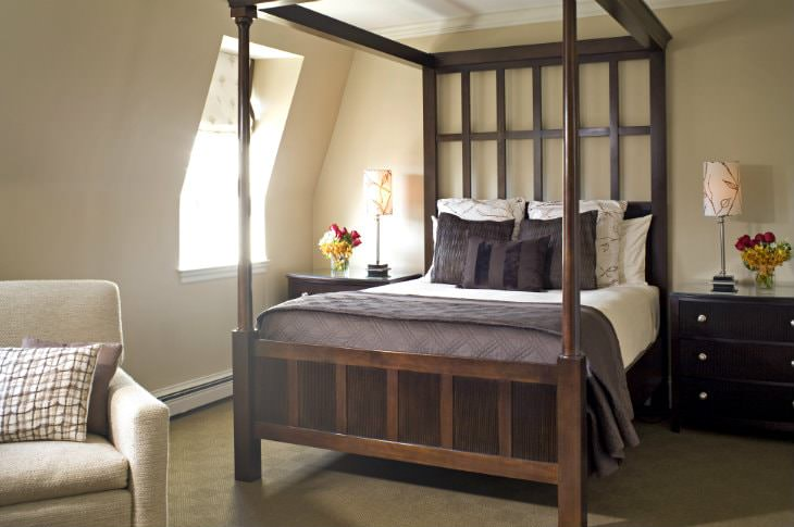 Elegant beige guest room with dark wood four-poster bed, and matching wood nightstands with lamps