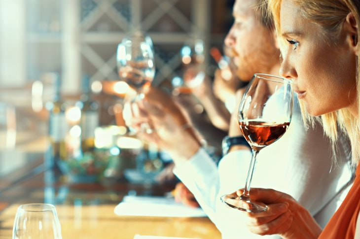 Woman sniffing a glass of red wine at a bar alongside several other people