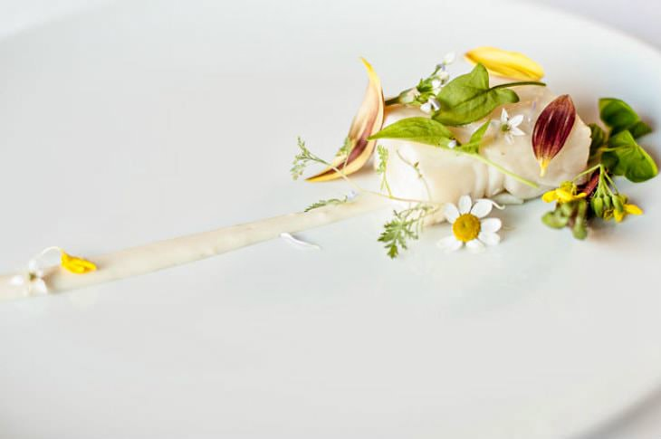 Artistic gourmet dish sprinkled with small delicate white, green and yellow flowers and leaves on a white plate