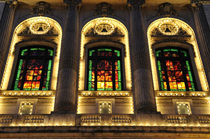 Ornately carved stone building lit up at night with tall arched windows, Grecian columns, and stained glass