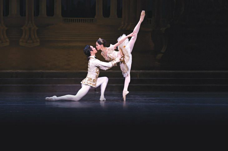 Male ballet dancer on one knee holding a female ballet dancer in Arabesque, both dressed in white and gold