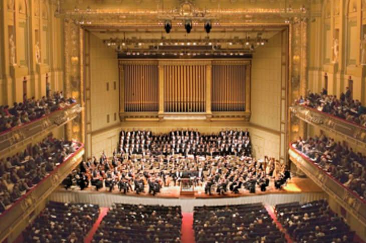 Elegant and elaborate auditorium with gold walls and tall ceilings filled with an orchestra and audience