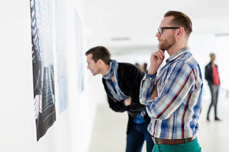 Two men contemplating a piece of art in a modern, white, brightly lit art gallery