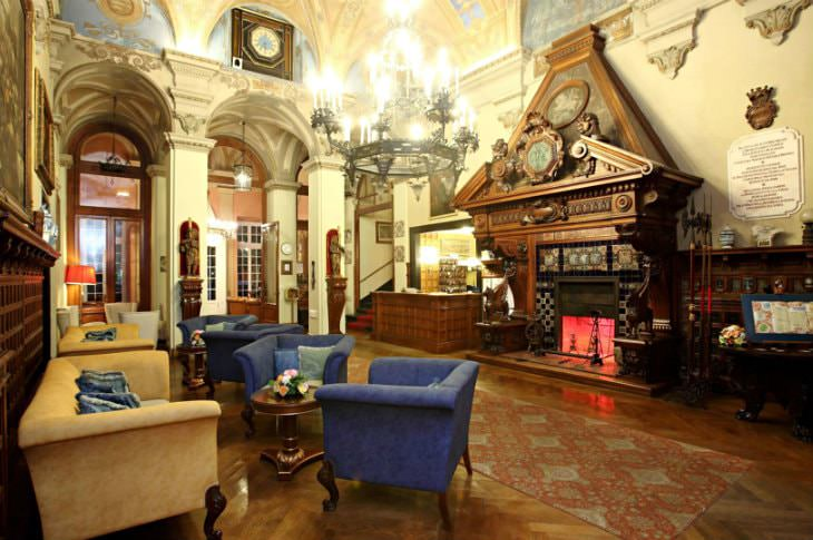 Elegant Italian hotel lobby with murals, arched doorways, elaborate chandelier, wood floors, fireplace and blue and gold seating