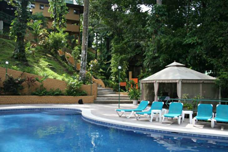 Clear blue swimming pool with turquoise chaise lounge chairs surrounded by lush greenery and a hilltop hotel